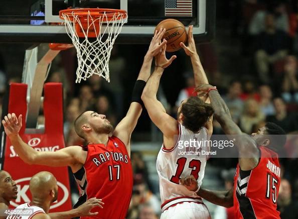 Jonas Valanciunas of the Toronto Raptors blocks a shot by Joakim Noah of the Chicago Bulls as Amir Johnson defends at the United Center on December...