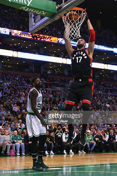 Jonas Valanciunas of the Toronto Raptors dunks over Amir Johnson of the Boston Celtics during the first quarter at TD Garden on March 23 2016 in...