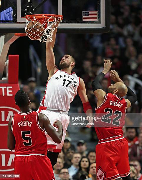 Jonas Valanciunas of the Toronto Raptors dunks over Bobby Portis and Taj Gibson of the Chicago Bulls at the United Center on February 19 2016 in...