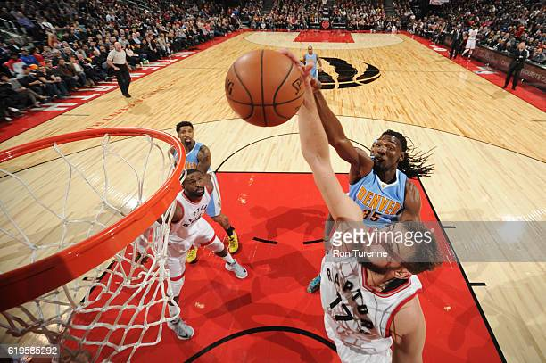 Jonas Valanciunas of the Toronto Raptors goes up for a rebound against Kenneth Faried of the Denver Nuggets during a game on October 31 2016 at the...