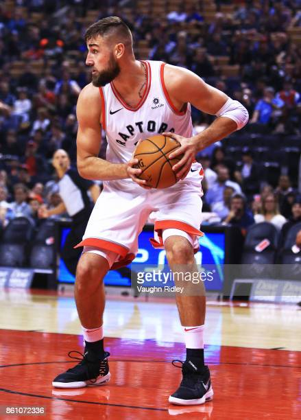 Jonas Valanciunas of the Toronto Raptors grabs a rebound during the first half of an NBA preseason game against the Detroit Pistons at Air Canada...