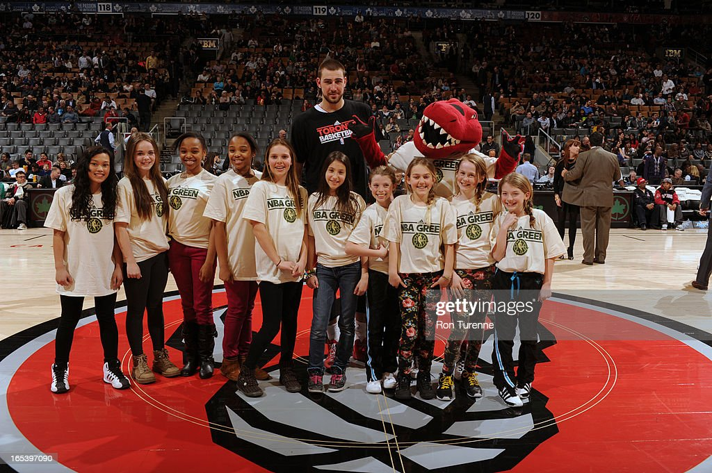 Jonas Valanciunas #17 of the Toronto Raptors poses with children and the Raptor for NBA GREEN Month prior to the game against the Washington Wizards during the game on April 3, 2013 at the Air Canada Centre in Toronto, Ontario, Canada.