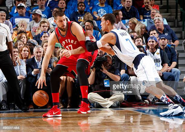 Jonas Valanciunas of the Toronto Raptors posts up against Dwight Powell of the Dallas Mavericks on November 3 2015 at the American Airlines Center in...