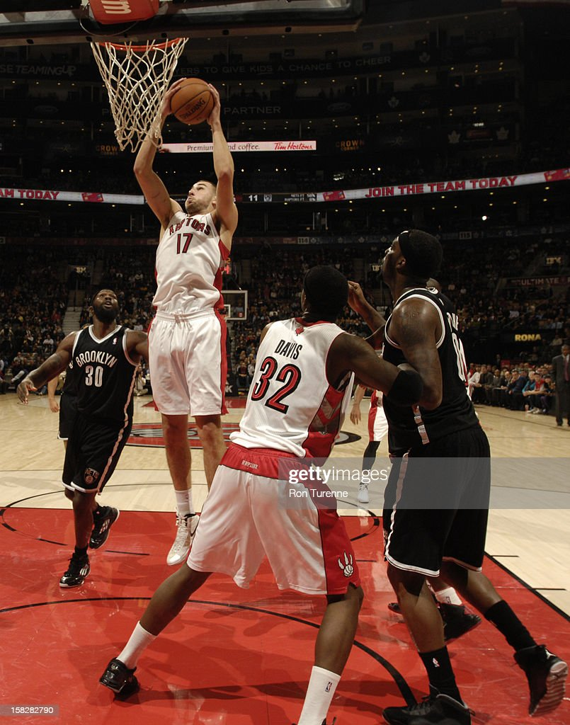 Jonas Valanciunas #17 of the Toronto Raptors pulls down a rebound against Reggie Evans #30 of the Brooklyn Nets on December 12, 2012 at the Air Canada Centre in Toronto, Ontario, Canada.