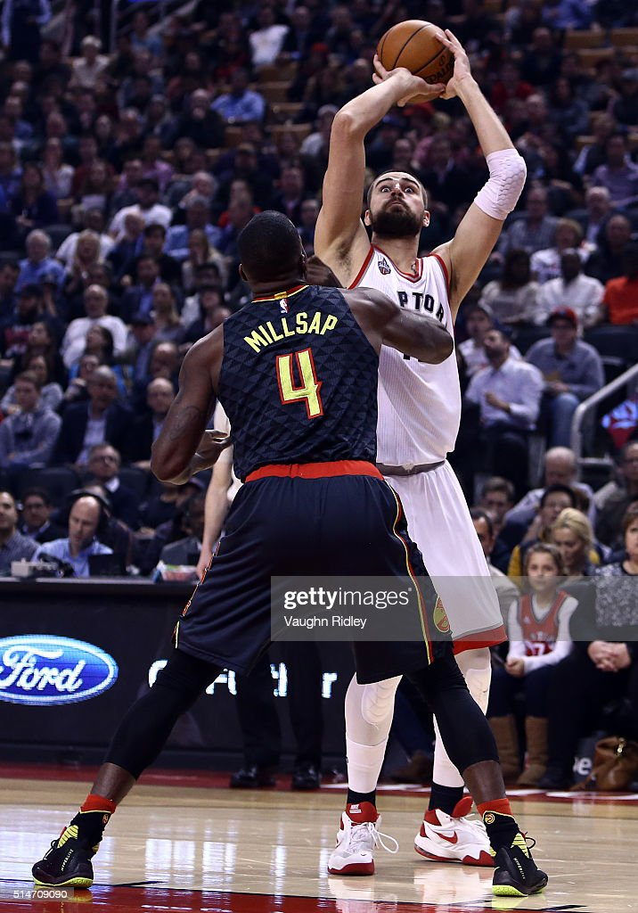 Jonas Valanciunas #17 of the Toronto Raptors shoots the ball as Paul Millsap #4 of the Atlanta Hawks defends during the first half of an NBA game at the Air Canada Centre on March 10, 2016 in Toronto, Ontario, Canada.
