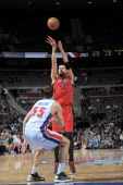 Jonas Valanciunas of the Toronto Raptors shoots the ball over Viacheslav Kravtsov of the Detroit Pistons during the game between the Detroit Pistons...