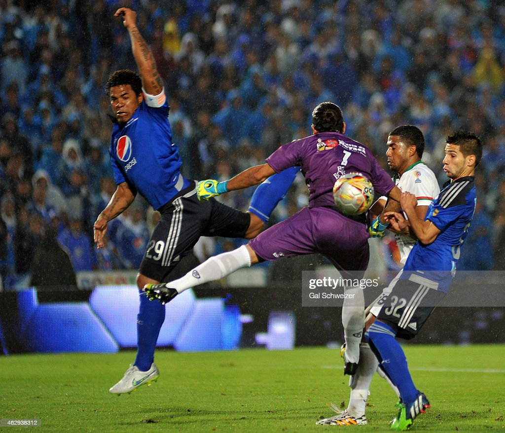 Jonathan Agudelo (R) and Roman Torres (L) of Millonarios vies for the ball with goalkeeper Juan Castillo (C) of Patriotas during a match between Millonarios and Patriotas FC as part of second round of Liga Aguila 2015 at Nemesio Camacho El Campin Stadium on February 07, 2015 in Bogota, Colombia.
