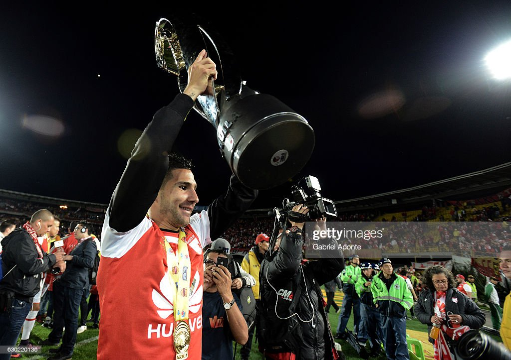 Jonathan Agudelo of Santa Fe lifts the trophy to celebrate after winning a second leg final match between Santa Fe and Deportes Tolima as part of Liga Aguila II 2016 at El Campin Stadium on December 18, 2016 in Bogota, Colombia.