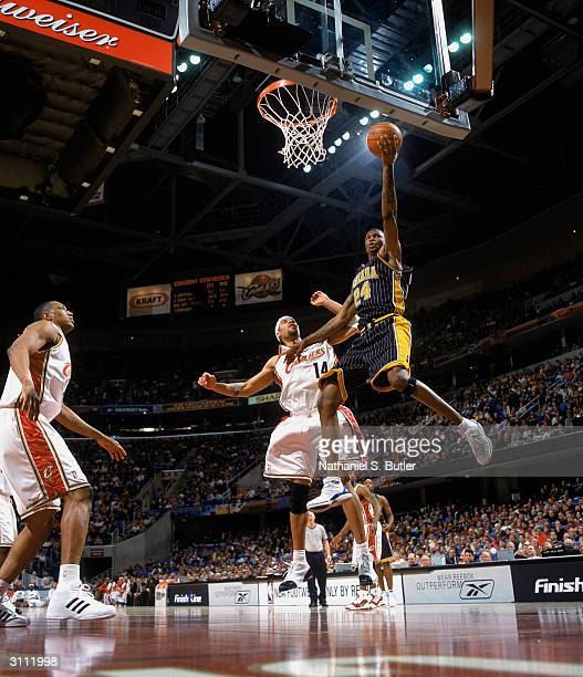 Jonathan Bender of the Indiana Pacers goes up for a layup over Ira Newble of the Cleveland Cavaliers during the game at Gund Arena on March 14 2004...
