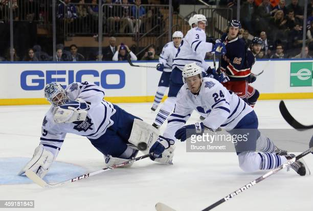 Jonathan Bernier and Peter Holland of the Toronto Maple Leafs dive to block a shot by JT Miller of the New York Rangers during the second period at...