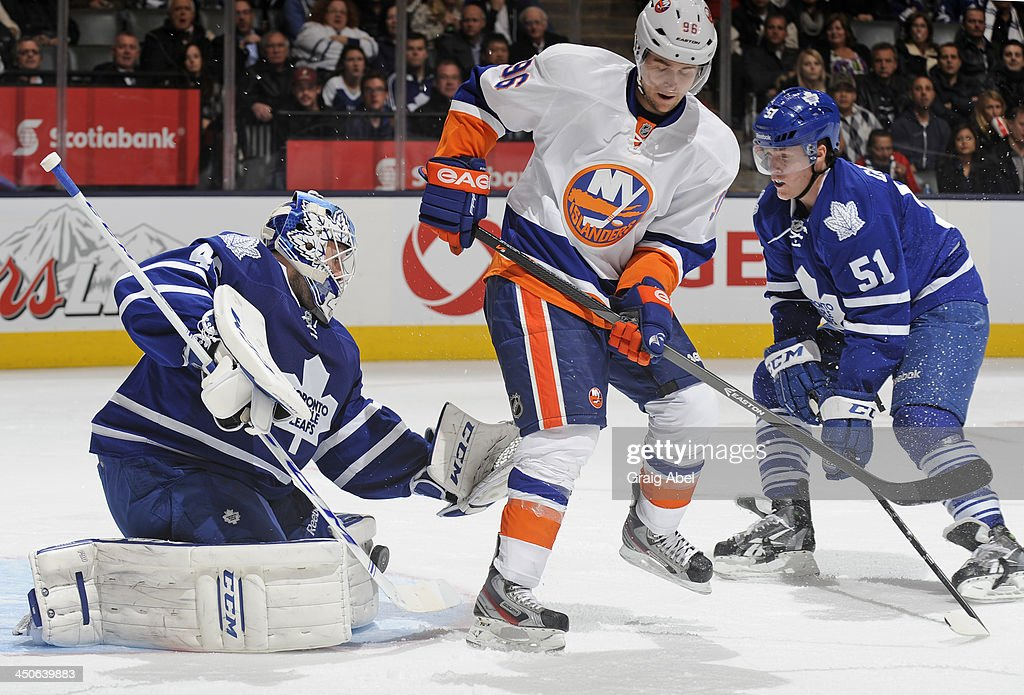 <a gi-track='captionPersonalityLinkClicked' href=/galleries/search?phrase=Jonathan+Bernier&family=editorial&specificpeople=540491 ng-click='$event.stopPropagation()'>Jonathan Bernier</a> #45 of the Toronto Maple Leafs makes a pad save as teammate <a gi-track='captionPersonalityLinkClicked' href=/galleries/search?phrase=Jake+Gardiner&family=editorial&specificpeople=4884939 ng-click='$event.stopPropagation()'>Jake Gardiner</a> #51 battles with Pierre-Marc Bouchard #96 of the New York Islanders during NHL game action November 19, 2013 at the Air Canada Centre in Toronto, Ontario, Canada.