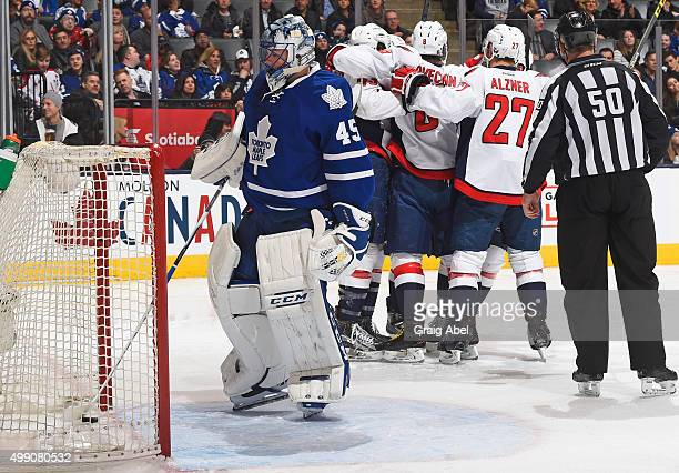 Jonathan Bernier of the Toronto Maple Leafs pulls the puck out of the net as of the Washington Capitals celebrate a second period goal during NHL...