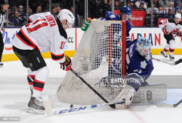 Jonathan Bernier of the Toronto Maple Leafs reaches out for a poke check as Stephen Gionta of the New Jersey Devils battles for the puck during NHL...