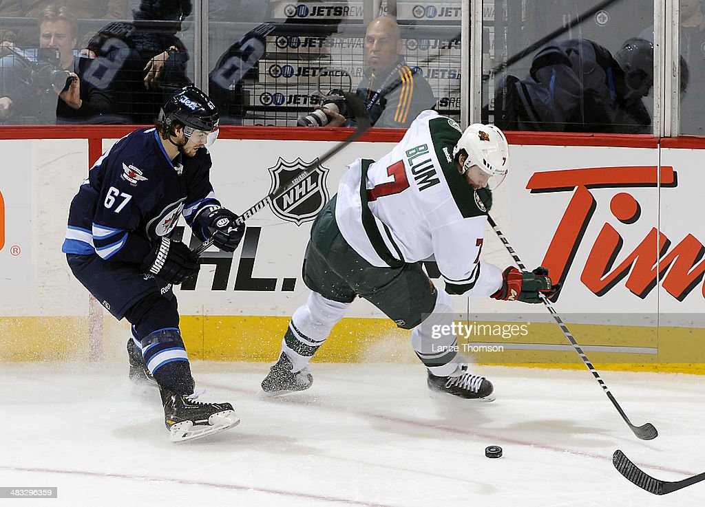 Jonathan Blum #7 of the Minnesota Wild plays the puck as <a gi-track='captionPersonalityLinkClicked' href=/galleries/search?phrase=Michael+Frolik&family=editorial&specificpeople=537965 ng-click='$event.stopPropagation()'>Michael Frolik</a> #67 of the Winnipeg Jets gives chase during second period action at the MTS Centre on April 7, 2014 in Winnipeg, Manitoba, Canada.