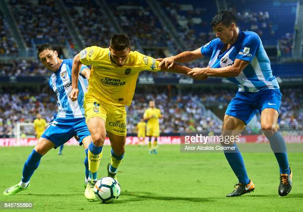 Jonathan Calleri of Union Deportiva Las Palmas competes for the ball with Federico Ricca of Malaga CF and Diego Gonzalez of Malaga CF during the La...