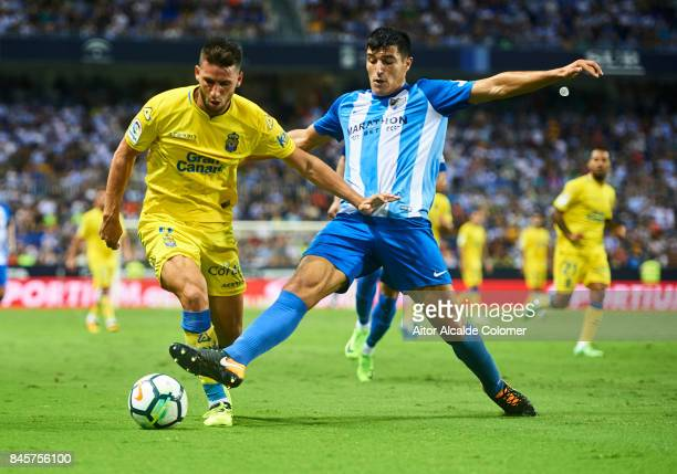 Jonathan Calleri of Union Deportiva Las Palmas competes for the ball with Diego Gonzalez of Malaga CF during the La Liga match between Malaga and Las...