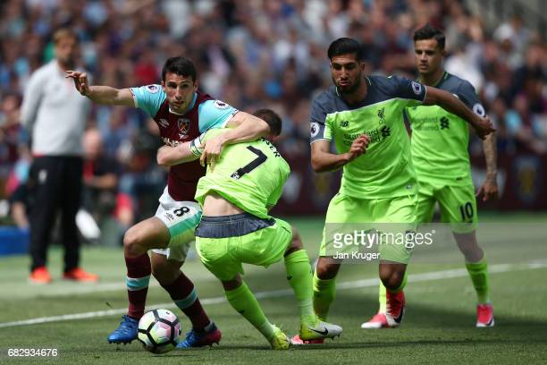 Jonathan Calleri of West Ham United attempts to get past James Milner of Liverpool during the Premier League match between West Ham United and...