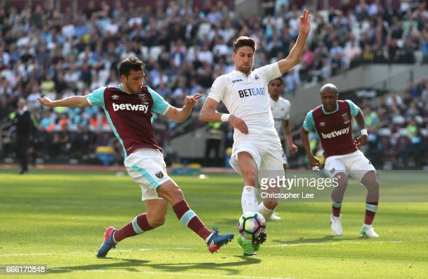 Jonathan Calleri of West Ham United shoots as Federico Fernandez of Swansea City attempts to block during the Premier League match between West Ham...
