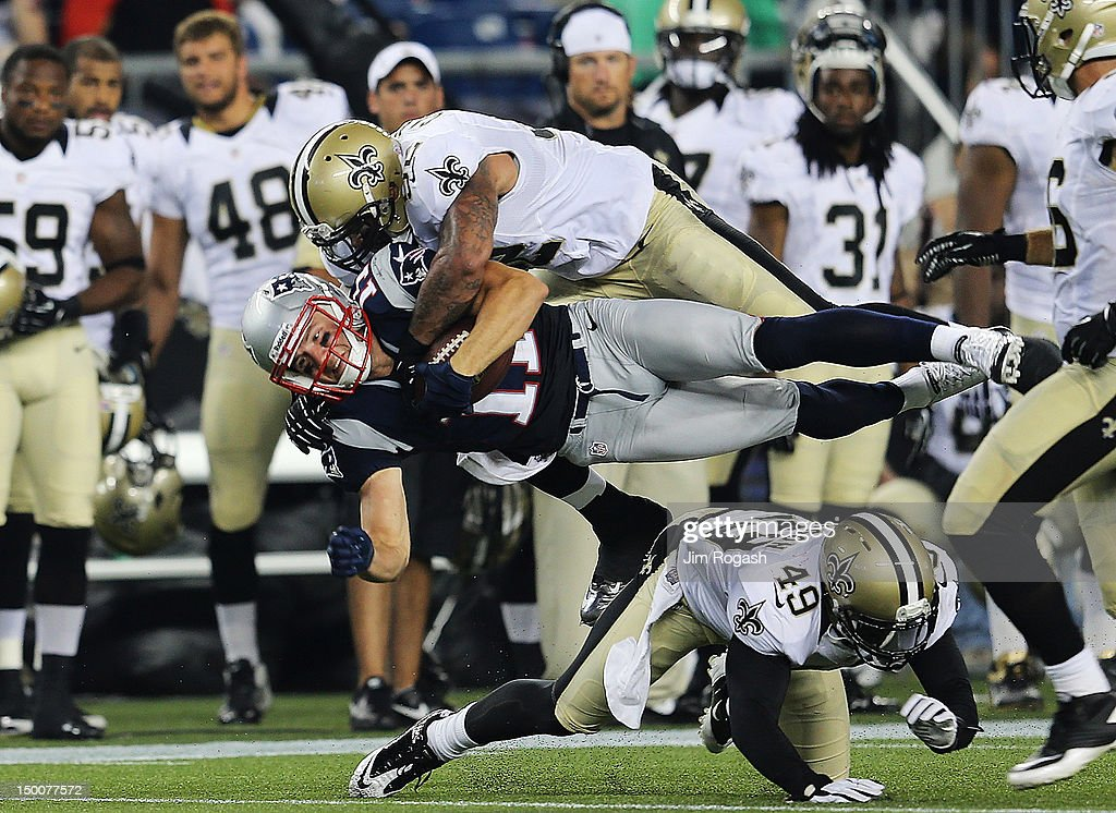 Jonathan Casillas #52 of the New Orleans Saints brings down <a gi-track='captionPersonalityLinkClicked' href=/galleries/search?phrase=Julian+Edelman&family=editorial&specificpeople=4489543 ng-click='$event.stopPropagation()'>Julian Edelman</a> #11 of the New England Patriots in the first half at Gillette Stadium on August 9, 2012 in Foxboro, Massachusetts.