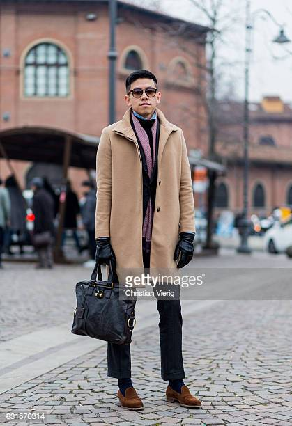 Jonathan Chiang is wearing a beige coat hand bag gloves loafers on January 12 2017 in Florence Italy