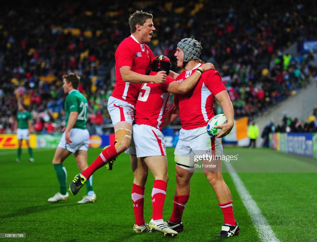 Jonathan Davies of Wales (R) celebrates with teammates <a gi-track='captionPersonalityLinkClicked' href=/galleries/search?phrase=Rhys+Priestland&family=editorial&specificpeople=4195648 ng-click='$event.stopPropagation()'>Rhys Priestland</a> (L) and <a gi-track='captionPersonalityLinkClicked' href=/galleries/search?phrase=Leigh+Halfpenny&family=editorial&specificpeople=4232760 ng-click='$event.stopPropagation()'>Leigh Halfpenny</a> after scoring their third try during quarter final one of the 2011 IRB Rugby World Cup between Ireland v Wales at Wellington Regional Stadium on October 8, 2011 in Wellington, New Zealand.
