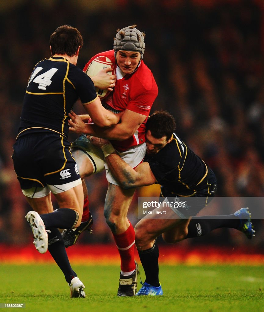 Jonathan Davies (C) of Wales is tackled by Lee Jones (L) and <a gi-track='captionPersonalityLinkClicked' href=/galleries/search?phrase=Sean+Lamont&family=editorial&specificpeople=241325 ng-click='$event.stopPropagation()'>Sean Lamont</a> (R) of Scotland during the RBS Six Nations match between Wales and Scotland at the Millenium Stadium on February 12, 2012 in Cardiff, Wales.