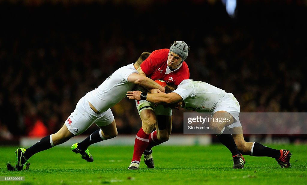 Jonathan Davies of Wales is tackled by Owen Farrell (L) and Tom Youngs (R) of England during the RBS Six Nations match between Wales and England at the Millennium Stadium in Cardiff, Wales