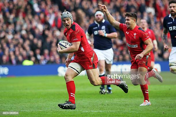 Jonathan Davies of Wales scores his team's second try as teammates Rhys Webb of Wales celebrates during the RBS Six Nations match between Scotland...