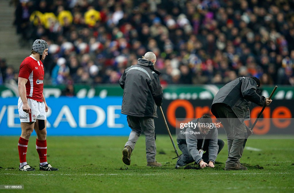Jonathan Davies of Wales watches as groundsmen try to repair the pitch during the RBS Six Nations match between France and Wales at Stade de France on February 9, 2013 in Paris, France.