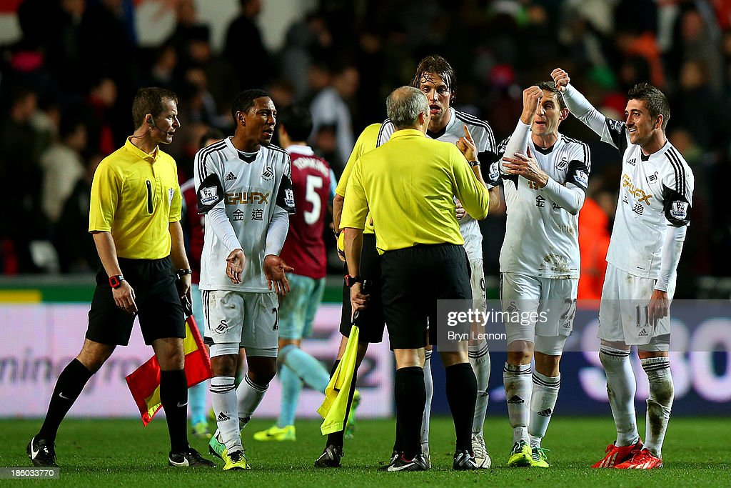 Jonathan de Guzman, Miguel Michu, Angel Rangel and Pablo Hernandez of Swansea protest to the referee and his assistants after the Barclays Premier League match between Swansea City and West Ham United at Liberty Stadium on October 27, 2013 in Swansea, Wales.