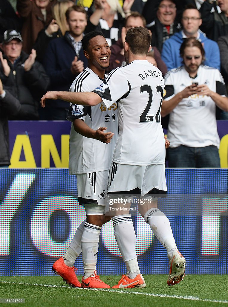 <a gi-track='captionPersonalityLinkClicked' href=/galleries/search?phrase=Jonathan+de+Guzman&family=editorial&specificpeople=674543 ng-click='$event.stopPropagation()'>Jonathan de Guzman</a> of Swansea City celebrates his second goal with Angel Rangel of Swansea City during the Barclays Premier League match between Swansea City and Norwich City at Liberty Stadium on March 29, 2014 in Swansea, Wales.