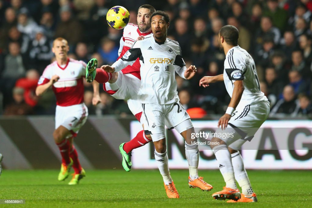<a gi-track='captionPersonalityLinkClicked' href=/galleries/search?phrase=Jonathan+de+Guzman&family=editorial&specificpeople=674543 ng-click='$event.stopPropagation()'>Jonathan de Guzman</a> (2R) of Swansea City challenges for the ball with Clint Dempsy of Fulham during the Barclays Premier League match between Swansea City and Fulham at the Liberty Stadium on January 28, 2014 in Swansea, Wales.