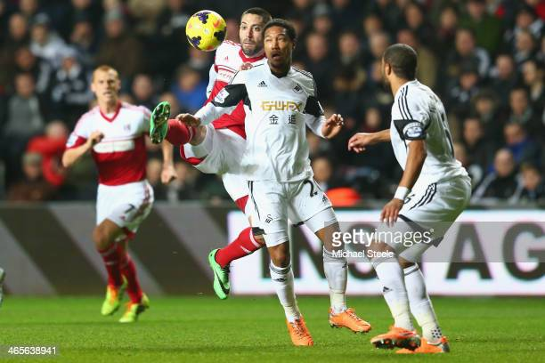 Jonathan de Guzman of Swansea City challenges for the ball with Clint Dempsy of Fulham during the Barclays Premier League match between Swansea City...