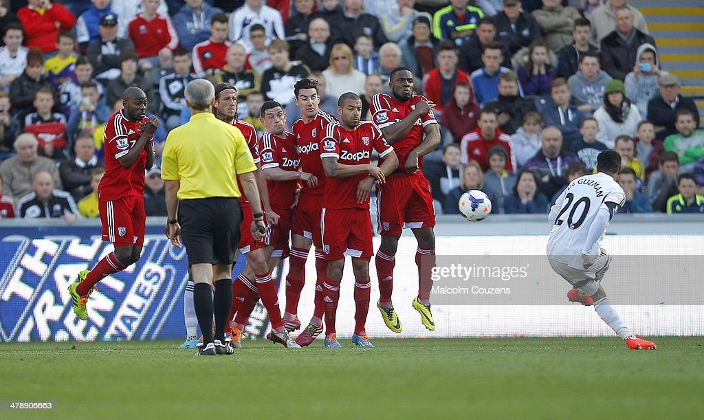 <a gi-track='captionPersonalityLinkClicked' href=/galleries/search?phrase=Jonathan+de+Guzman&family=editorial&specificpeople=674543 ng-click='$event.stopPropagation()'>Jonathan de Guzman</a> of Swansea City curls a free-kick over the West Bromwich Albion defensive wall during the Barclays Premier League match between Swansea City and West Bromwich Albion at The Liberty Stadium on March 15, 2014 in Swansea, Wales.