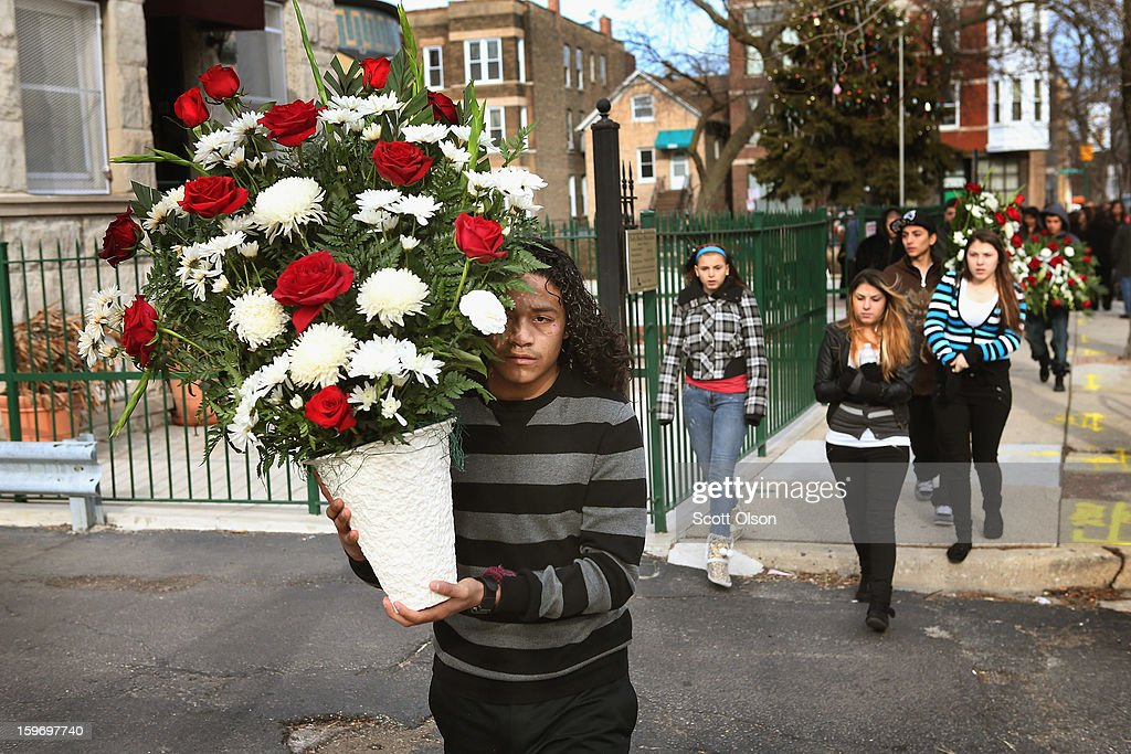 Jonathan Dorantes carries flowers home from the church following a funeral mass for his brother Rey on January 18, 2013 in Chicago, Illinois. Rey Dorantes, 14, died after being shot six times while he was sitting on the front porch of his home while talking on the phone on January 11. Dorantes's murder was the 21st homicide recorded in Chicago for 2013, a city which saw more than 500 homicides in 2012.
