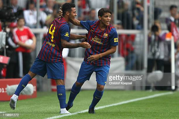 Jonathan Dos Santos of Barcelona celebrates the second goal with Thiago Alcantara during the Audi Cup match between FC Barcelona and International de...