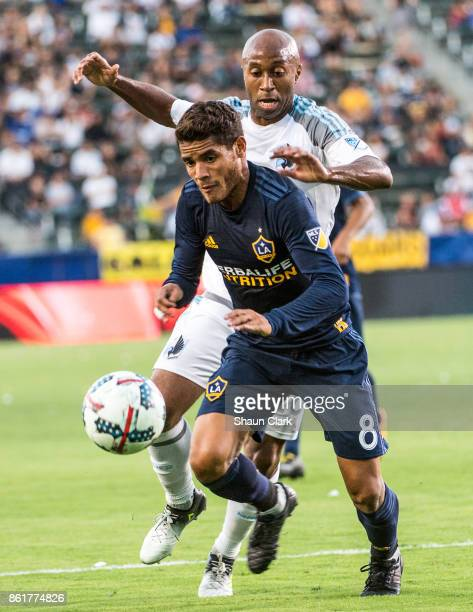 Jonathan dos Santos of Los Angeles Galaxy battles Collen Warner of Minnesota United during the Los Angeles Galaxy's MLS match against Minnesota...
