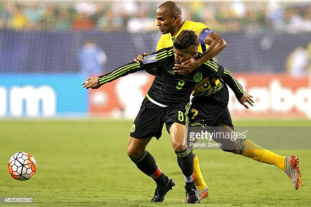 Jonathan Dos Santos of Mexico and Andre Clennon of Jamaica battle for the ball in the second half during the CONCACAF Gold Cup Final at Lincoln...