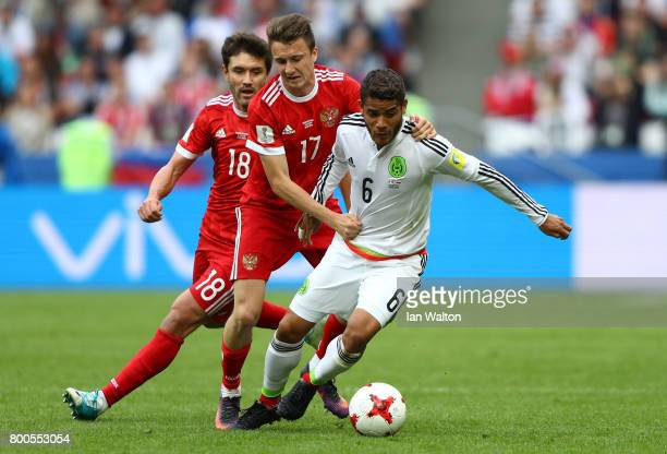 Jonathan Dos Santos of Mexico controls the ball under pressure of Aleksandr Golovin of Russia during the FIFA Confederations Cup Russia 2017 Group A...