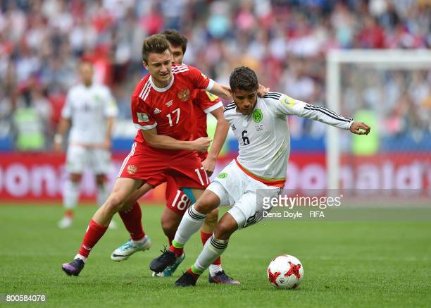 Jonathan Dos Santos of Mexico is tackled by Aleksandr Golovin of Russia during the Group A FIFA Confederation Cup match between Mexico and Russia at...