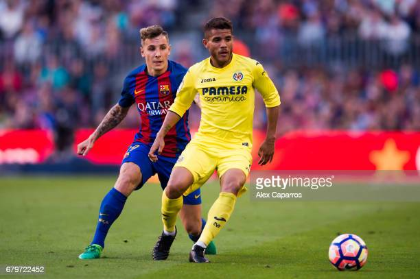 Jonathan dos Santos of Villarreal CF competes for the ball with Lucas Digne of FC Barcelona during the La Liga match between FC Barcelona and...