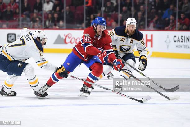 Jonathan Drouin of the Montreal Canadiens skates with the puck under pressure from Benoit Pouliot and Ryan O'Reilly of the Buffalo Sabres in the NHL...