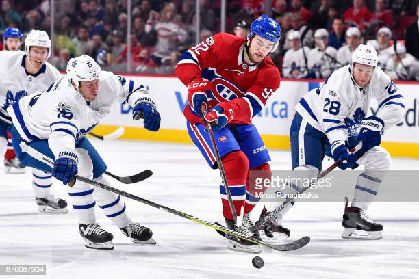 Jonathan Drouin of the Montreal Canadiens tries to skate the puck past Matt Martin and Connor Brown of the Toronto Maple Leafs during the NHL game at...