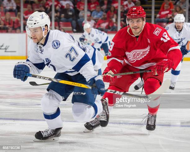 Jonathan Drouin of the Tampa Bay Lightning skates up ice in front of Robbie Russo of the Detroit Red Wings during an NHL game at Joe Louis Arena on...