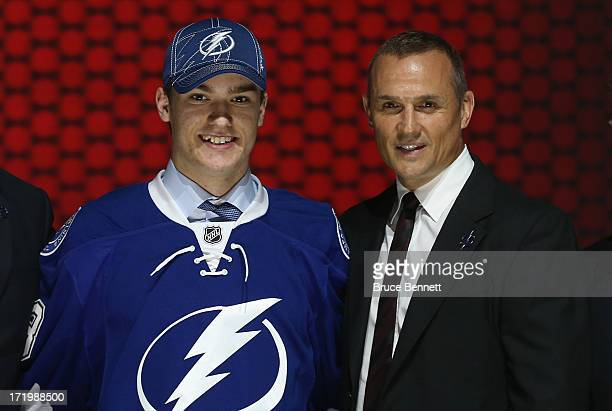 Jonathan Drouin puts on his jersey with Steve Yzerman Vice President and General Manager after being selected number three overall in the first round...