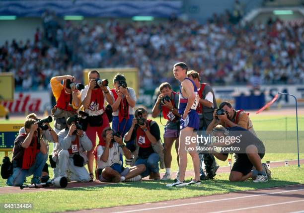 Jonathan Edwards of Great Britain surrounded by photographers after setting a world record whilst winning the triple jump event at the World...