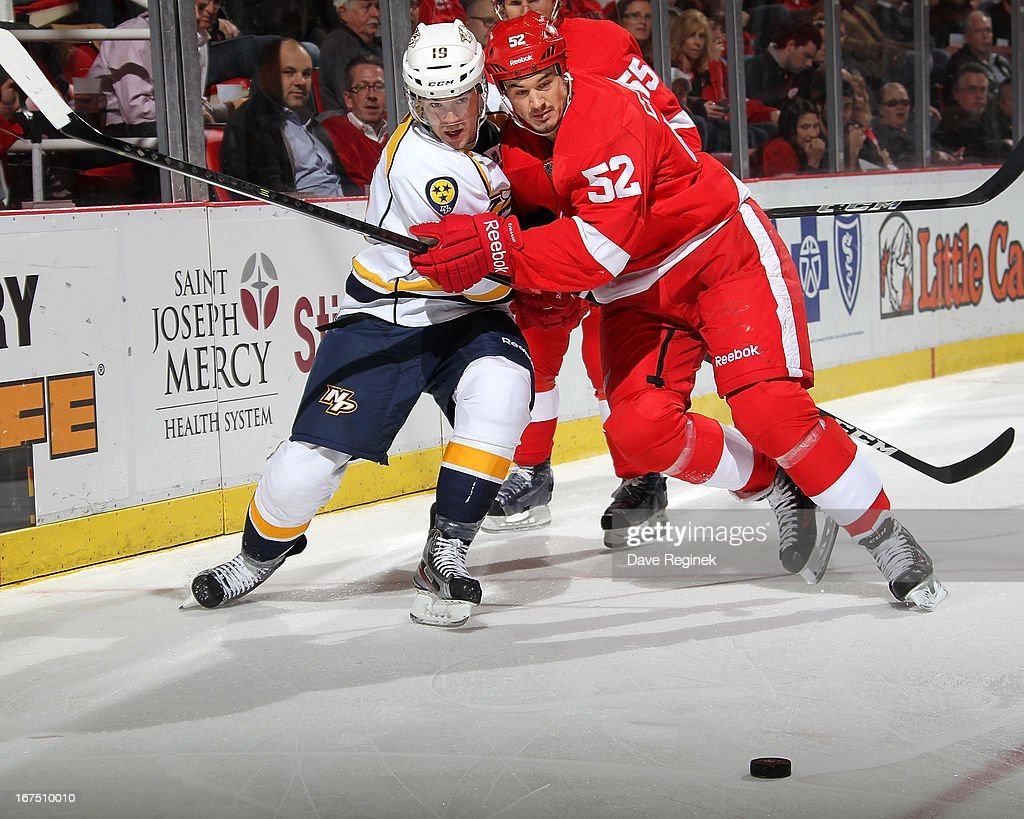 Jonathan Ericsson of the Detroit Red Wings and Bobby Butler of the Nashville Predators battle for the puck during a NHL game at Joe Louis Arena on...