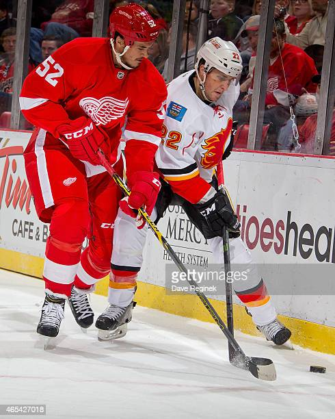 Jonathan Ericsson of the Detroit Red Wings and Drew Shore of the Calgary Flames battle for the puck in the corner during a NHL game on March 6 2015...