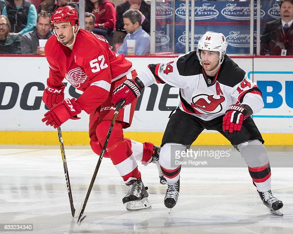 Jonathan Ericsson of the Detroit Red Wings fights for position with Adam Henrique of the New Jersey Devils during an NHL game at Joe Louis Arena on...