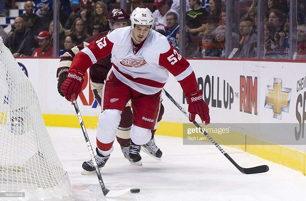 <a gi-track='captionPersonalityLinkClicked' href=/galleries/search?phrase=Jonathan+Ericsson&family=editorial&specificpeople=2538498 ng-click='$event.stopPropagation()'>Jonathan Ericsson</a> #52 of the Detroit Red Wings picks up the loose puck behind the net while being chased by <a gi-track='captionPersonalityLinkClicked' href=/galleries/search?phrase=Jannik+Hansen&family=editorial&specificpeople=741716 ng-click='$event.stopPropagation()'>Jannik Hansen</a> #36 of the Vancouver Canucks during the second period of NHL action on March 16, 2013 at Rogers Arena in Vancouver, British Columbia, Canada.
